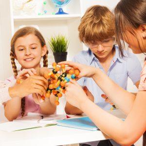 three children doing crafts